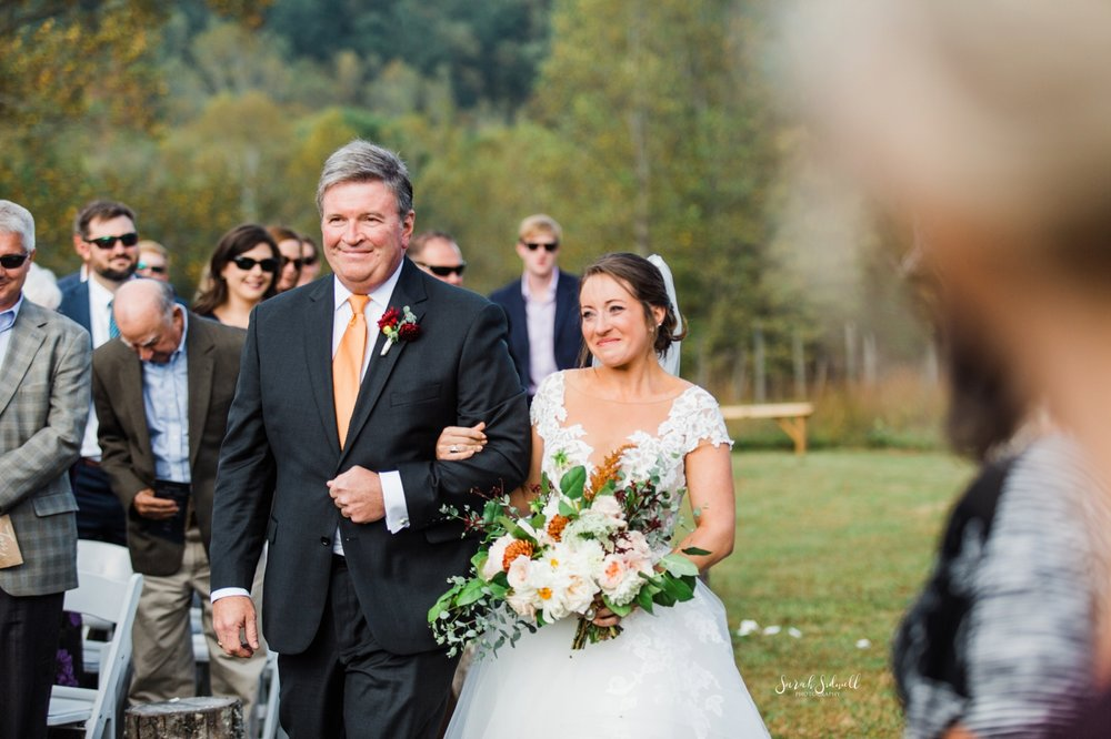 A father walks his daughter down the aisle for her wedding.