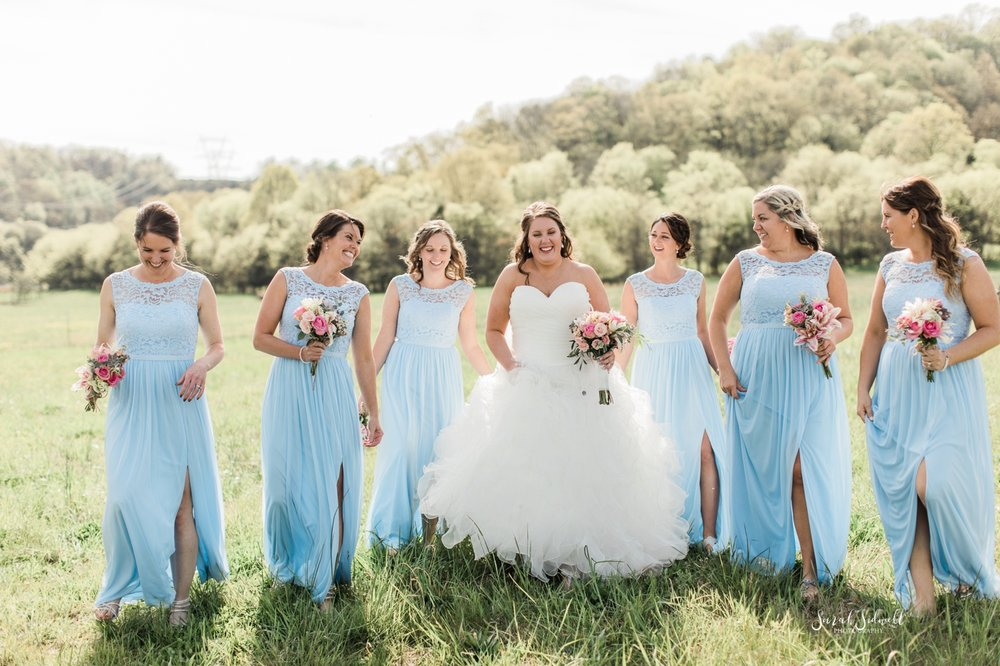 A bride laughs with her bridal party.