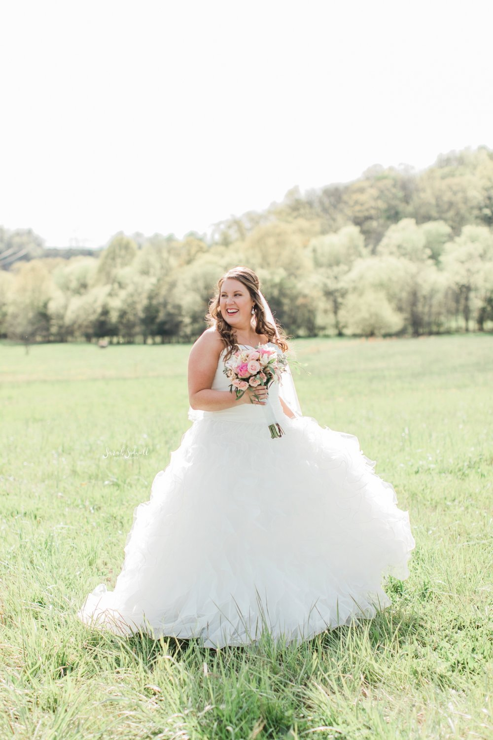 A bride stays in a green field, holding her bouquet.
