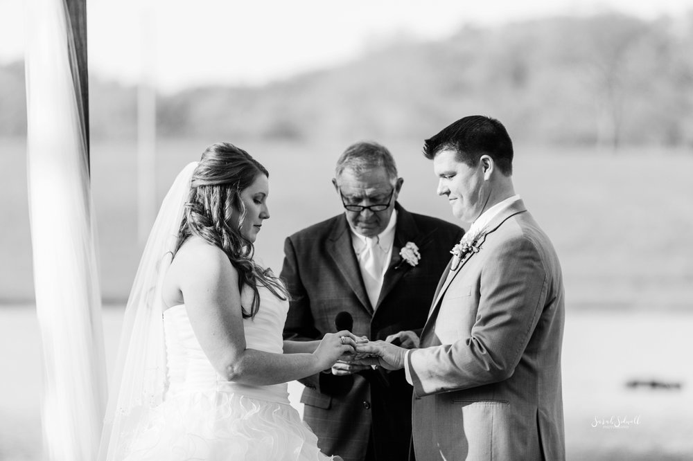 A bride and groom say their vows while holding hands.