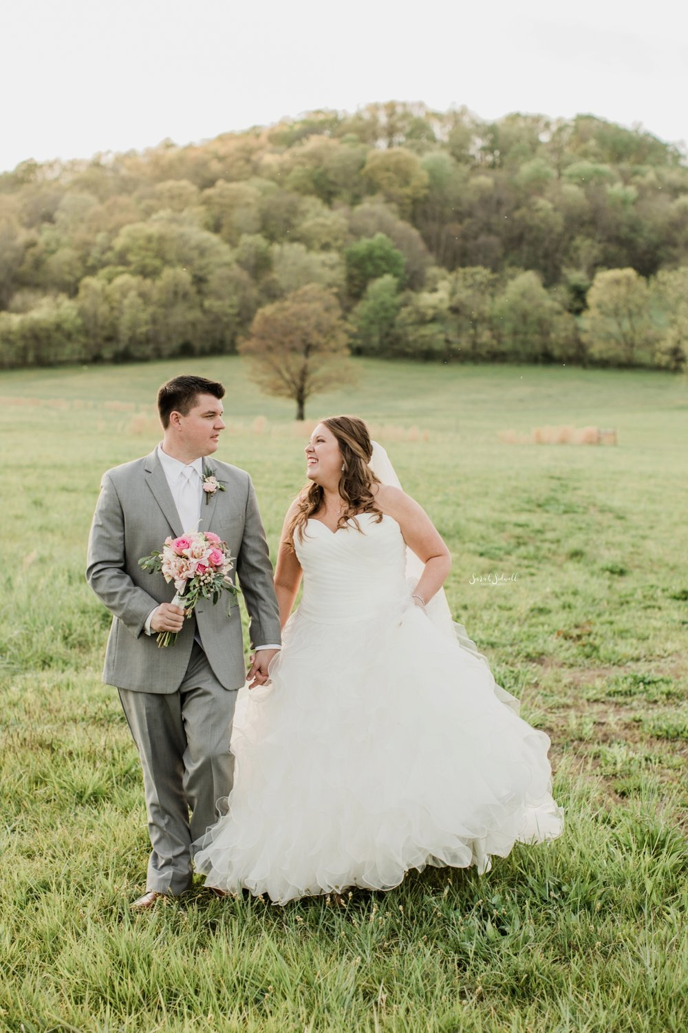 A bride and groom twirl in a green field.