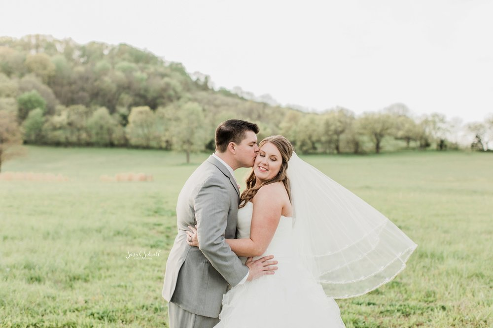 A groom kisses his bride in a green field of grass.