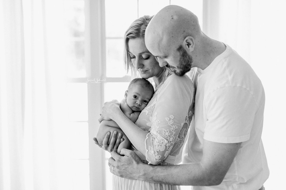 A man hugs his wife from behind as she holds their baby.