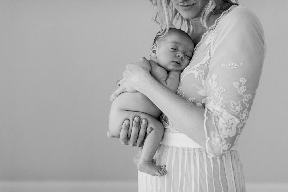 A mother gently cradles her newborn close to her.