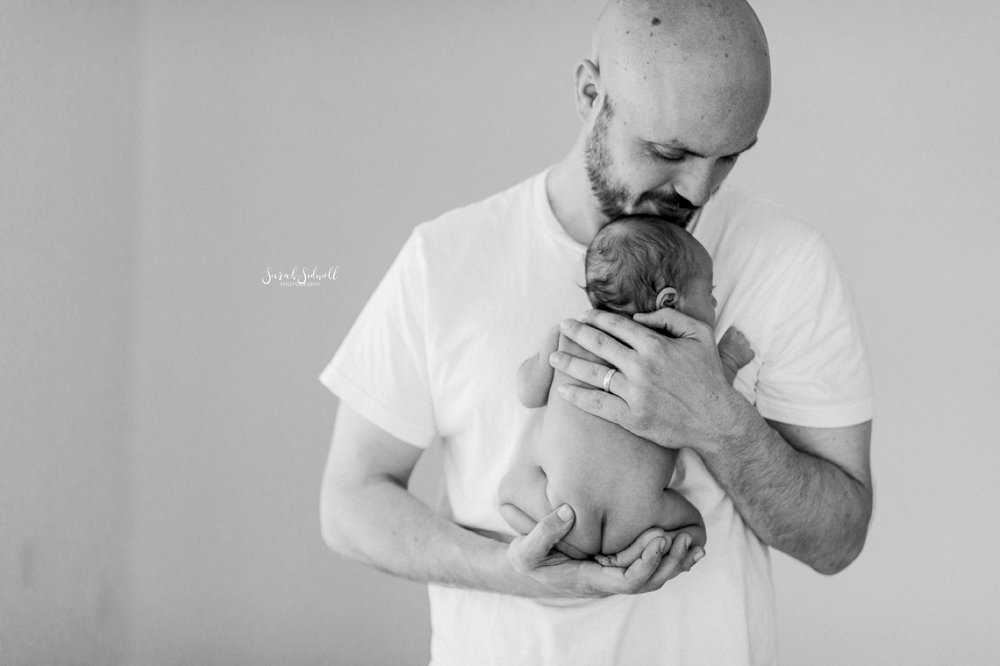 A man holds his newborn baby close to his chest.
