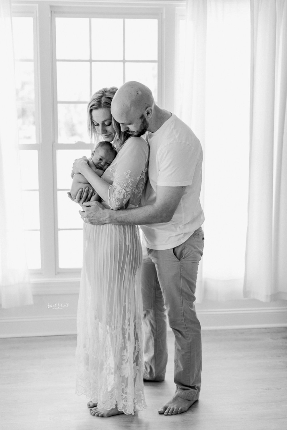 A man embraces his wife and newborn baby.