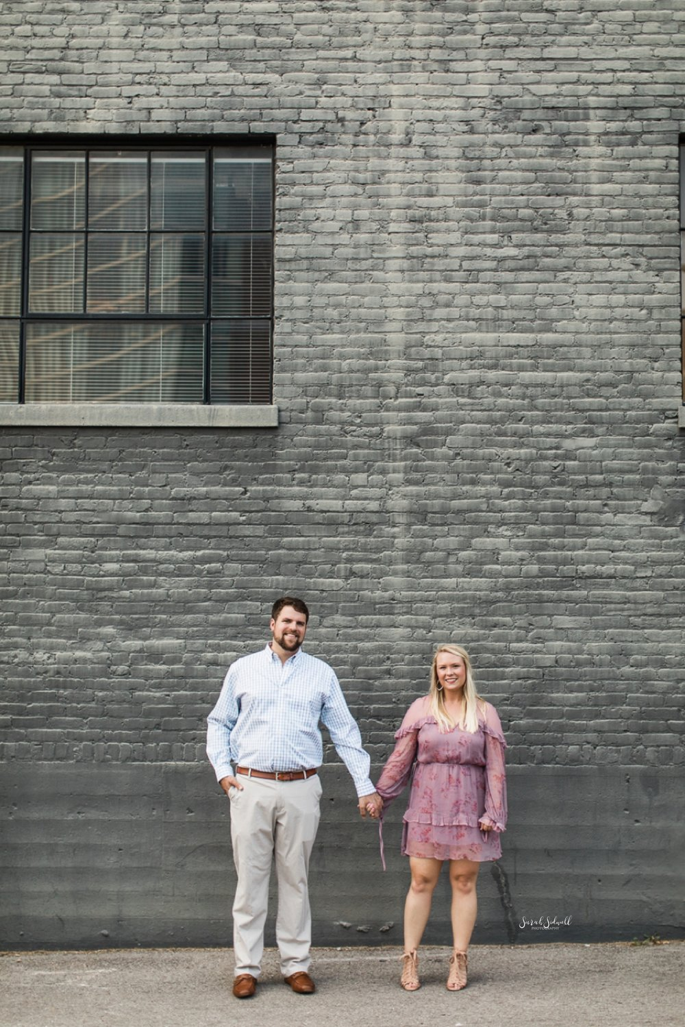 A couple hold hands in front of a grey brick building.