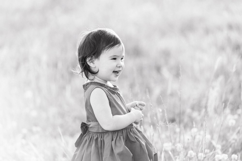 A baby stands in a grassy field, smiling into the distance.