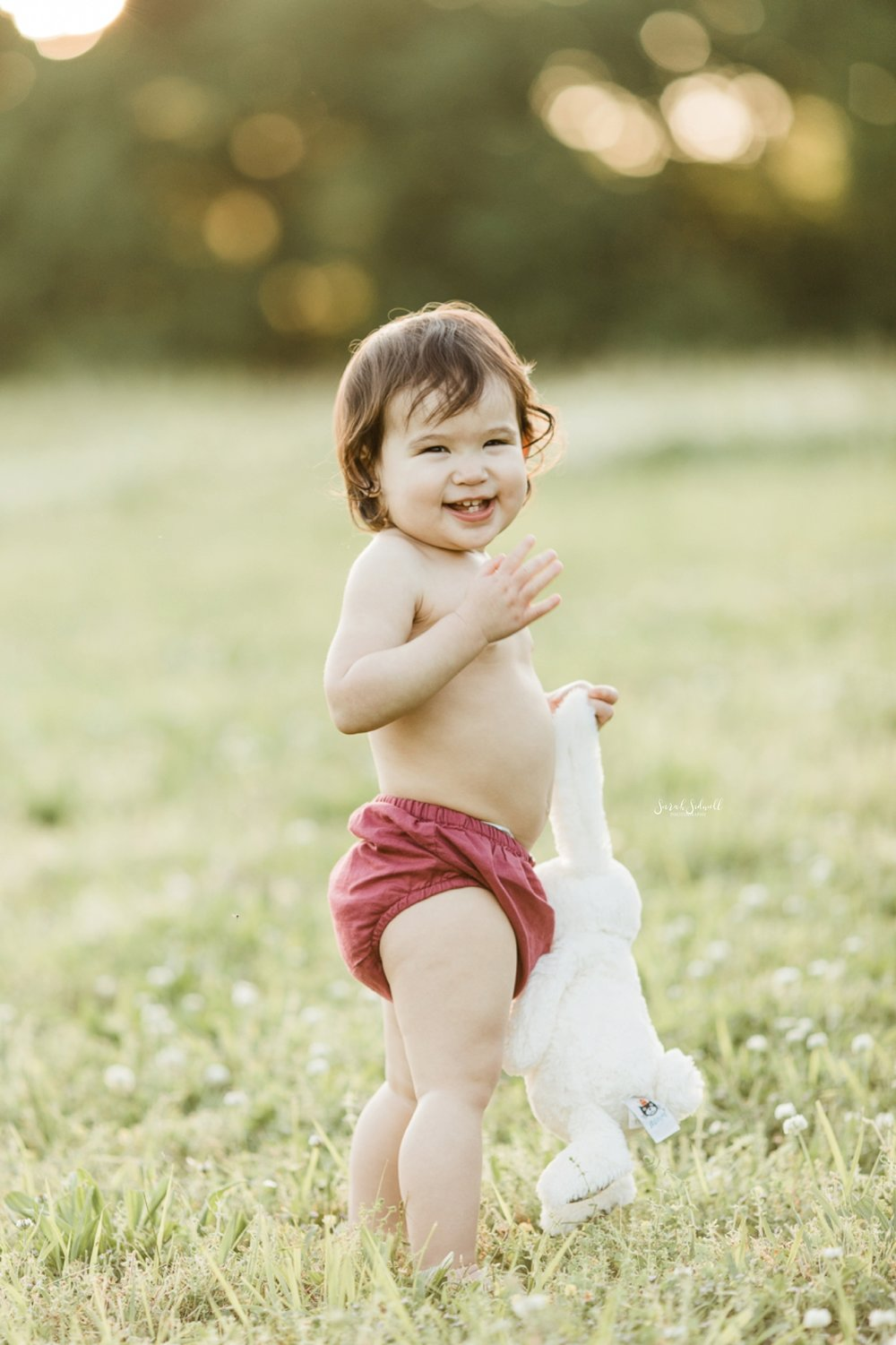 A baby wearing red bloomers holds her dress in her hands.