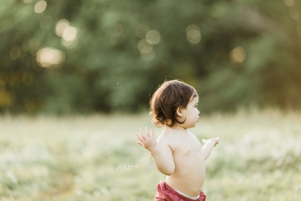 A baby wearing only bloomers walks through a grassy field.