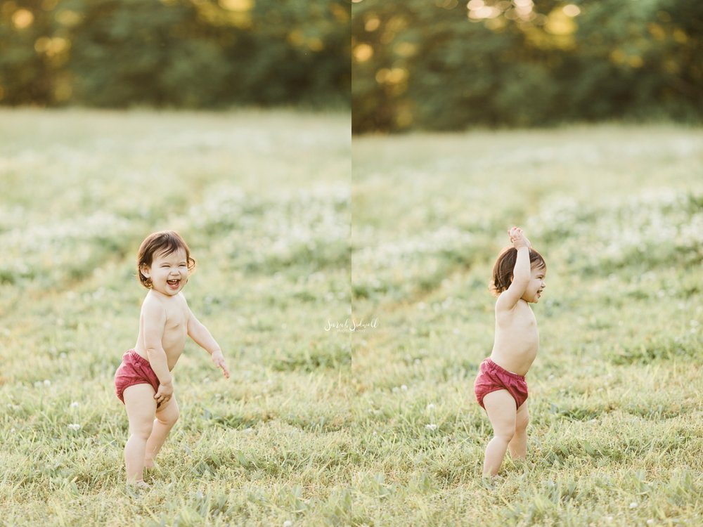 A baby plays in a grassy field wearing only bloomers.