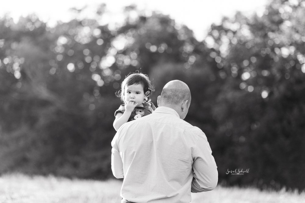 A toddler looks over her daddy's shoulder as the holds her.