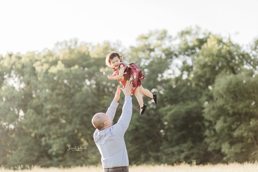 A man throws his toddler up into the air as he plays with her.