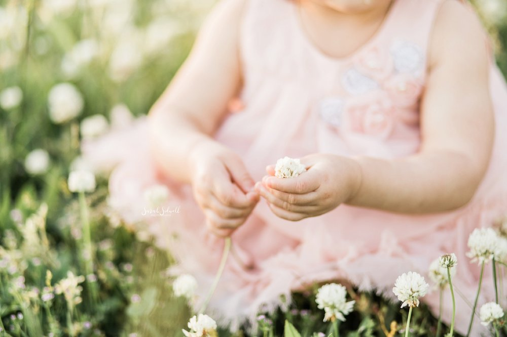 A toddler wearing a pink dress bends down to pick some white flowers.