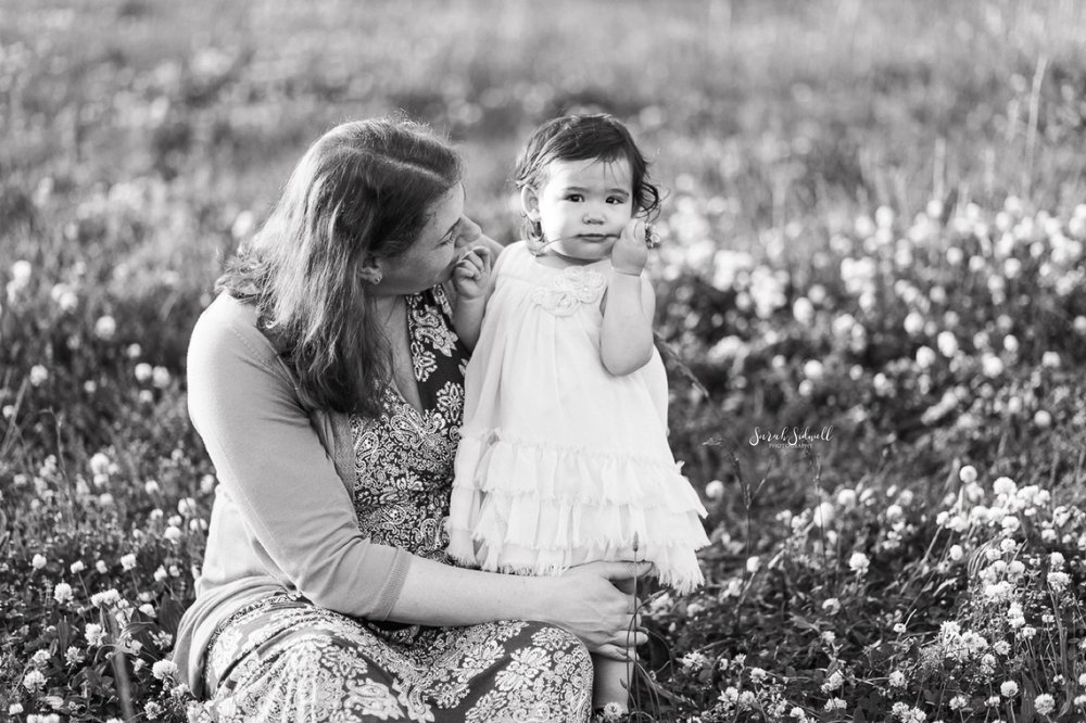 A mother kneels to her toddler as they sit in a field of white flowers.