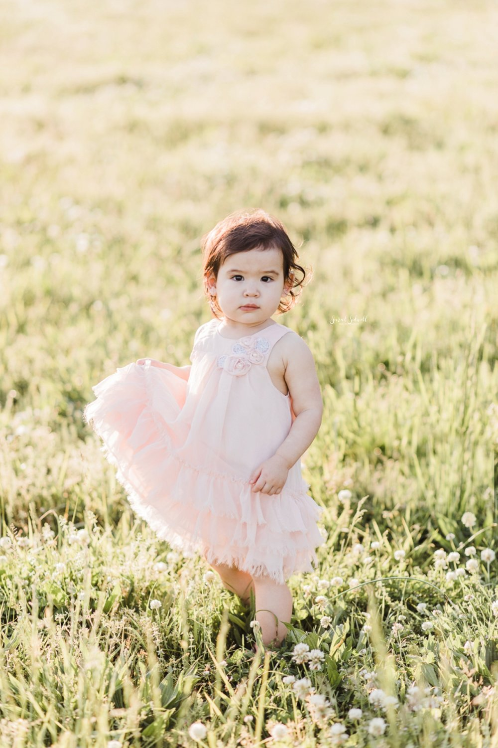 A toddler holds her pink dress in her hands as she walks.