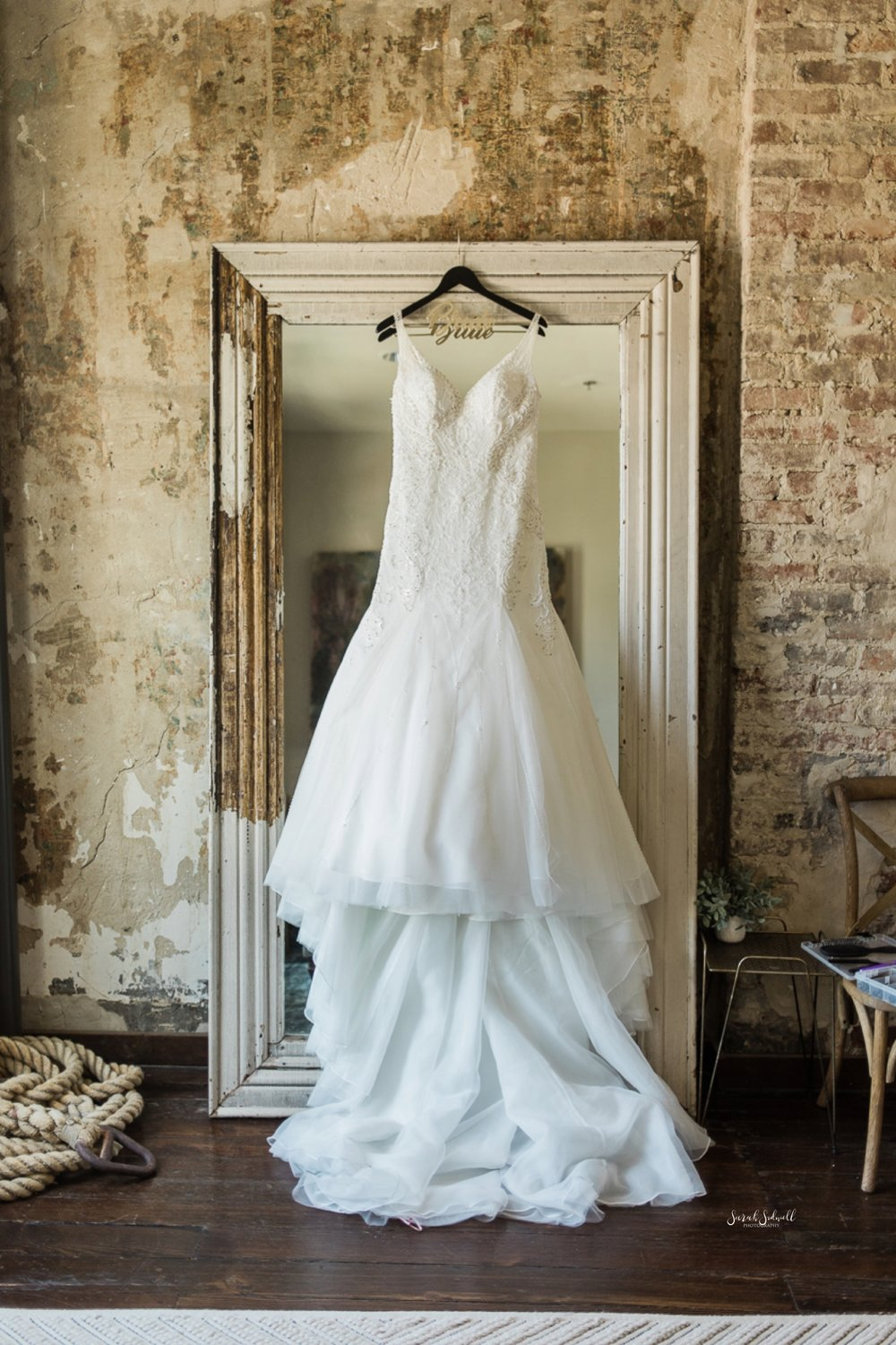 A wedding dress is hanging in a doorway of a venue.