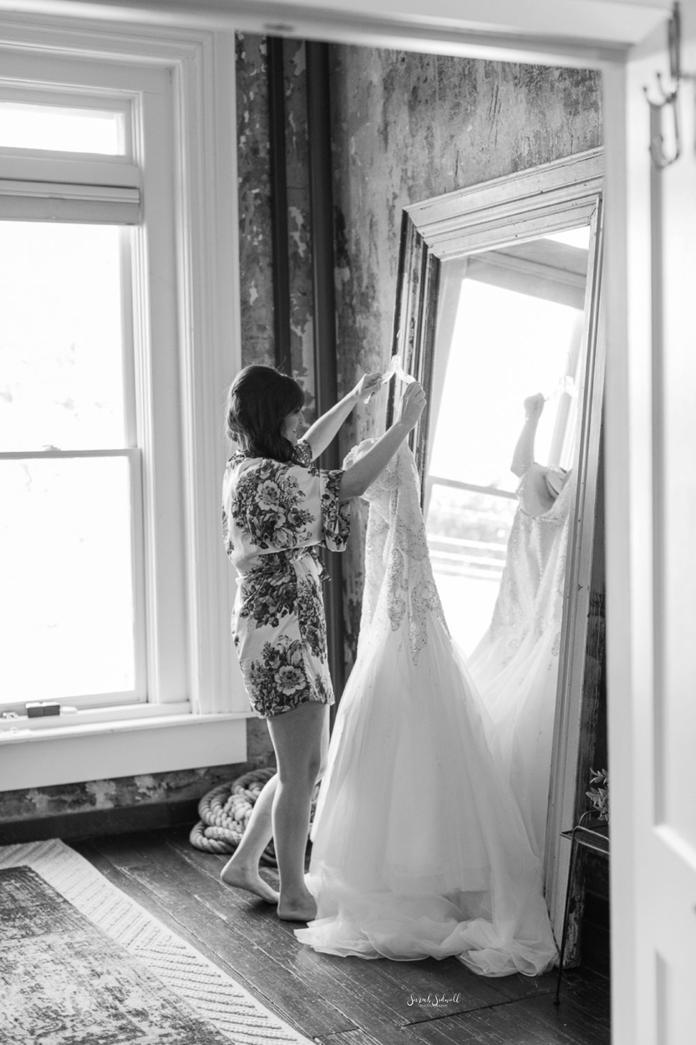 A bridesmaid hangs a bride's wedding dress up in a doorway.