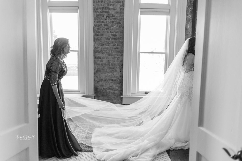 A bride's long veil is straightened out.