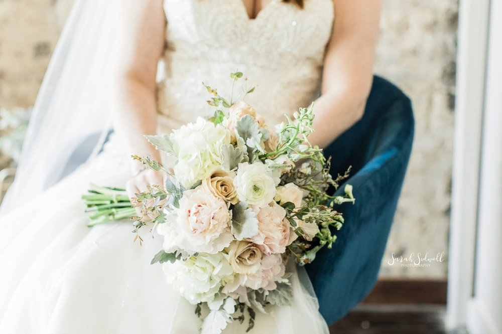 A bride holds her bouquet in her lap.