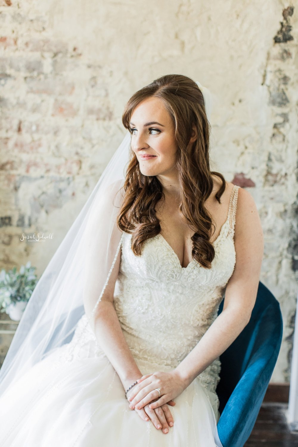 A woman sits in a chair while wearing her wedding dress.