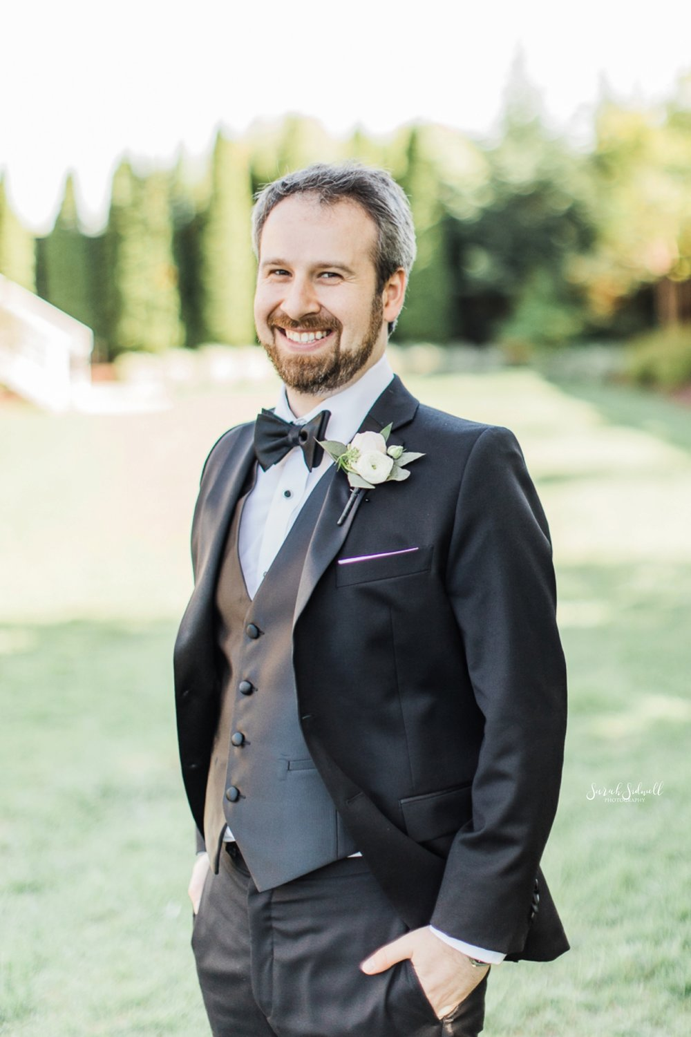 A man wears a tux for his wedding and puts his hand in his pocket.