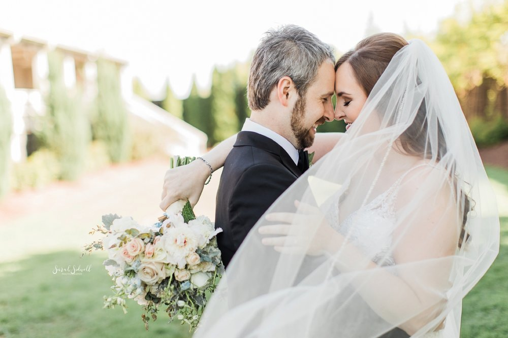 A bride hugs her groom around the neck as she holds her flowers.