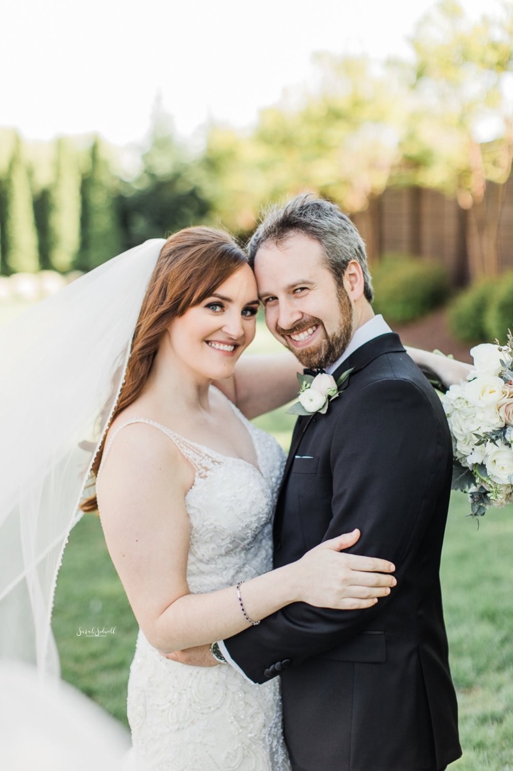 A man wraps his arms around his bride and smiles.