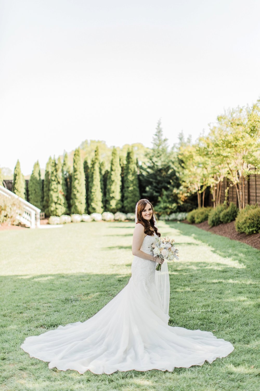 A bride stands in a green field with her dress spread out.