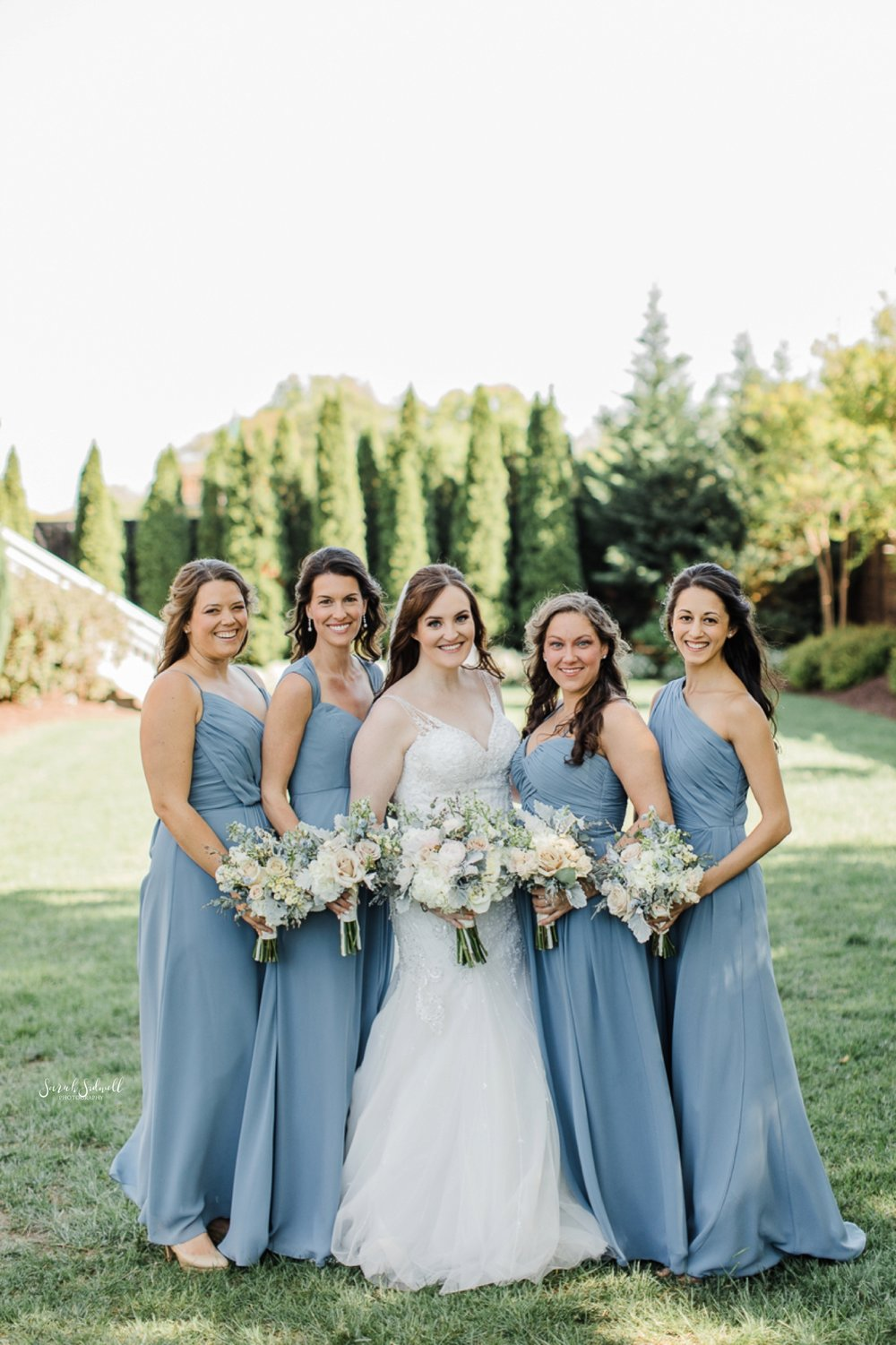 A bride stands with her bridal party and smiles.