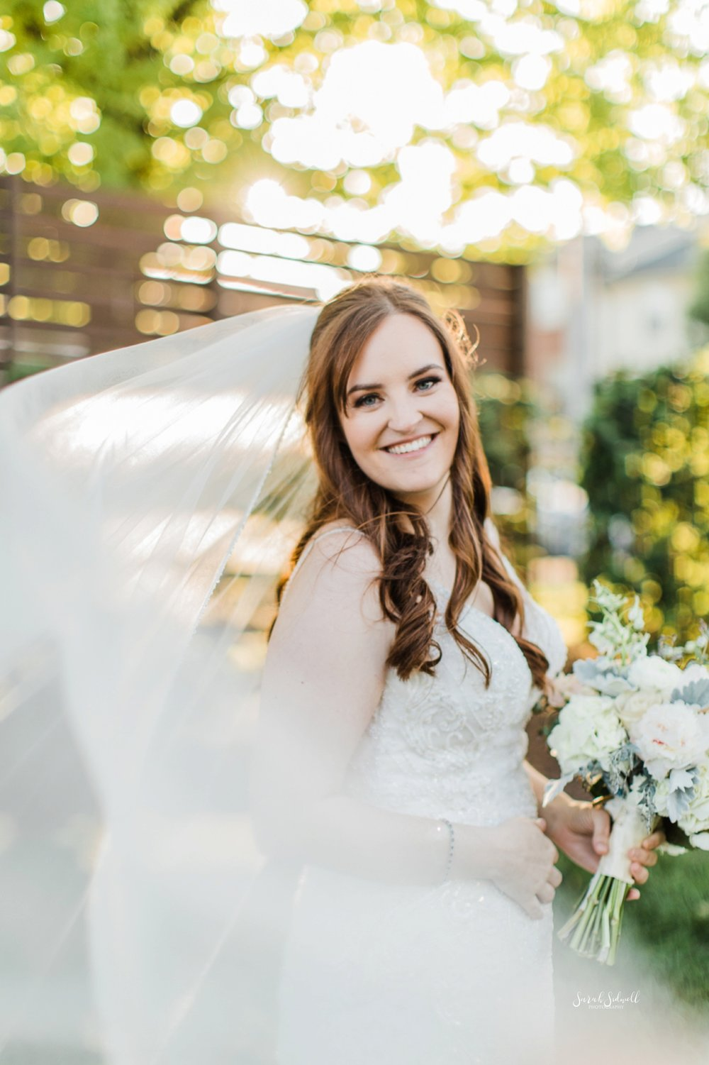A bride's veil flows around her as she smiles.
