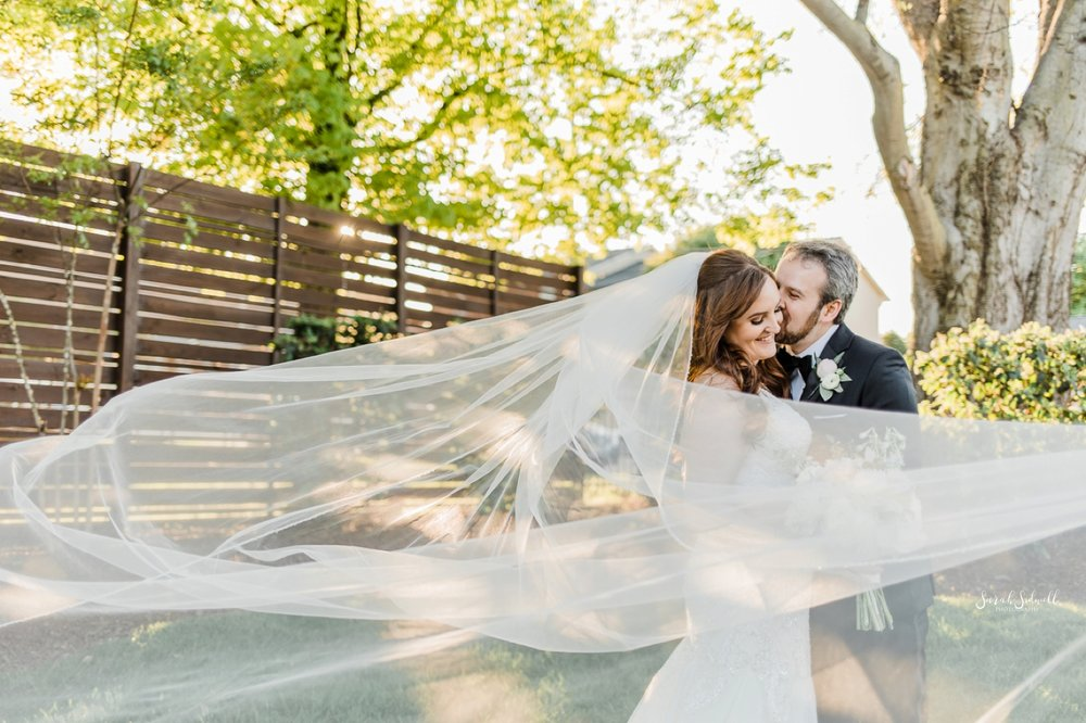 A bride's veil blows in the wind as her groom kisses her.