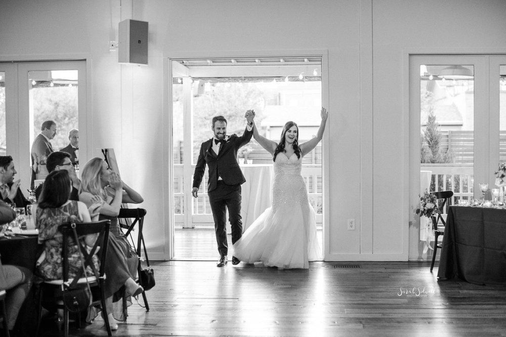 A bride and groom celebrate as they walk into their venue.