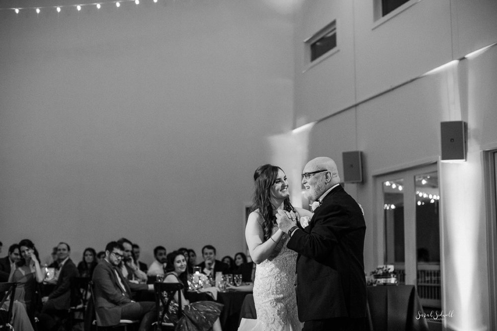 A woman dances with her father at her wedding.