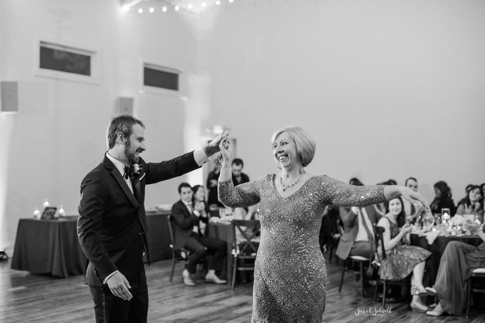 A man dances with his mother as his wedding.