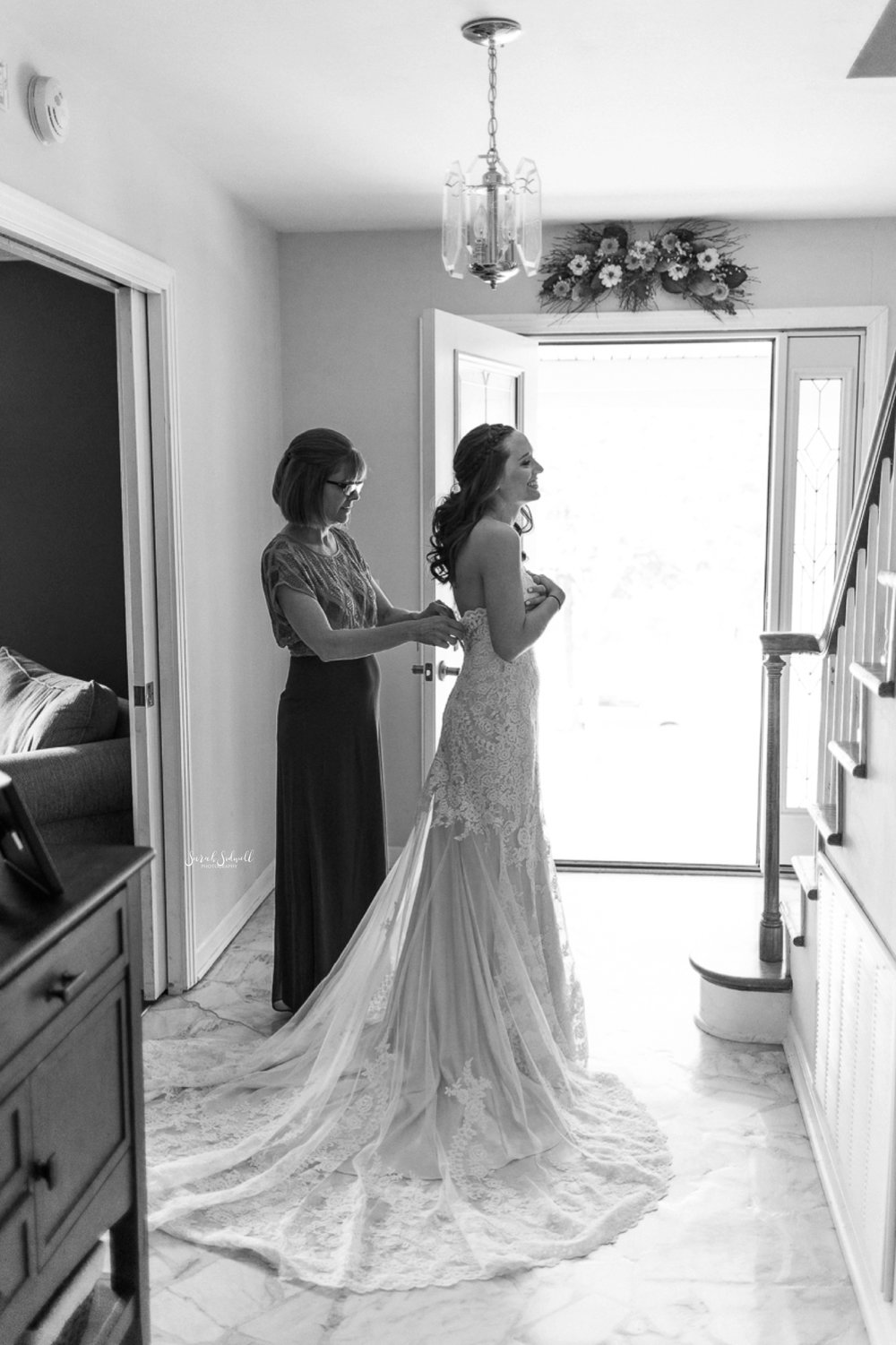 A bride gets into her dress for her wedding day.