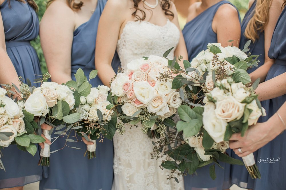 A bridal party holds out their flowers in a big bunch.