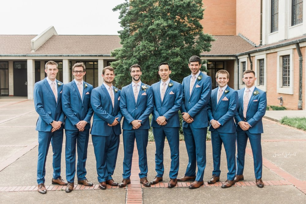 Groomsmen in blue suits stand in a line together.
