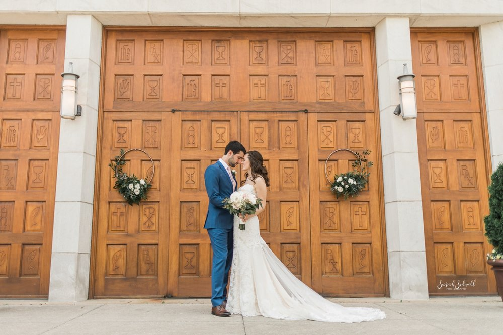 A groom kisses his bride in front of large wooden doors.