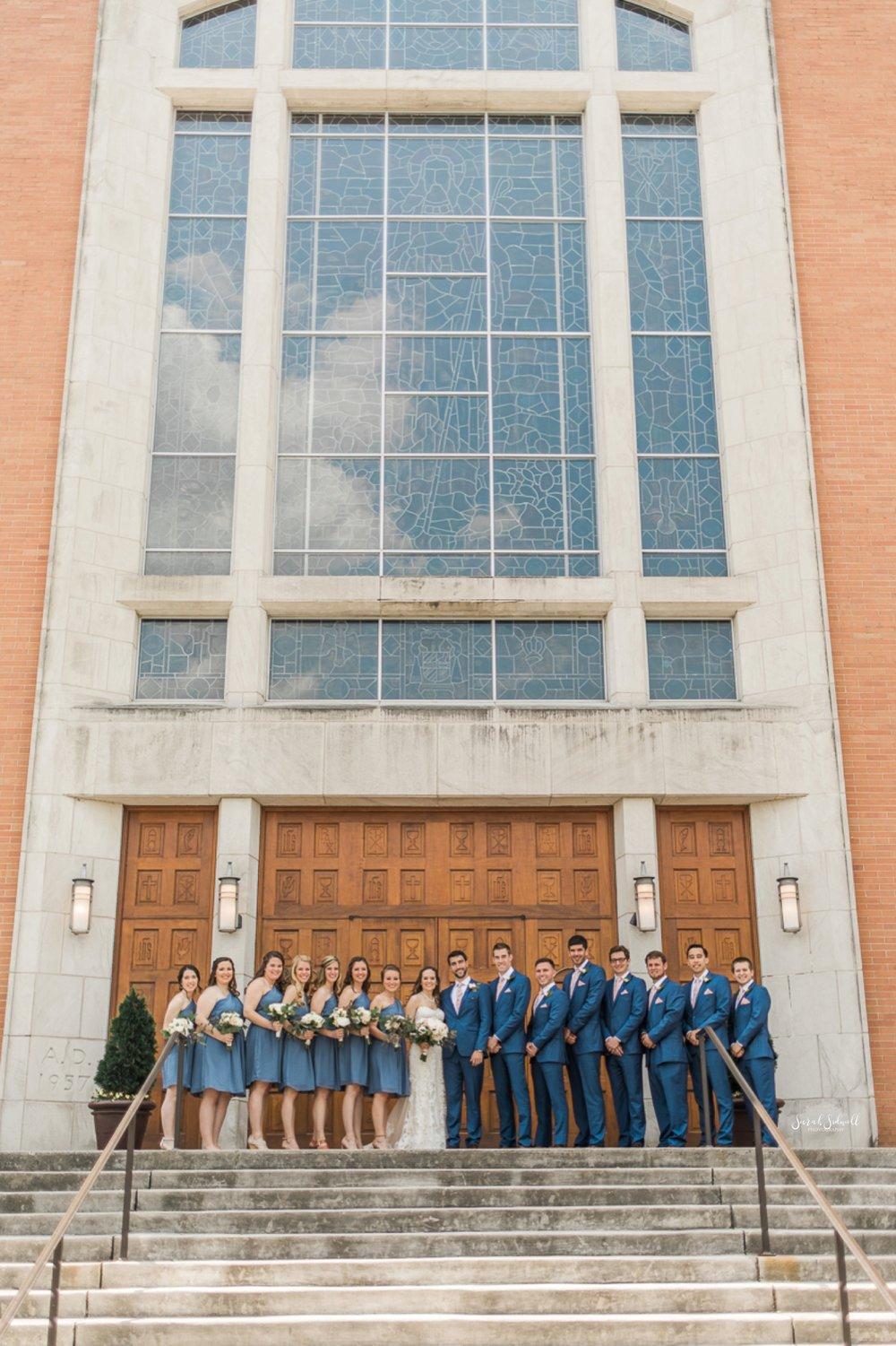 A wedding party stands in front of a tall building with tall windows.