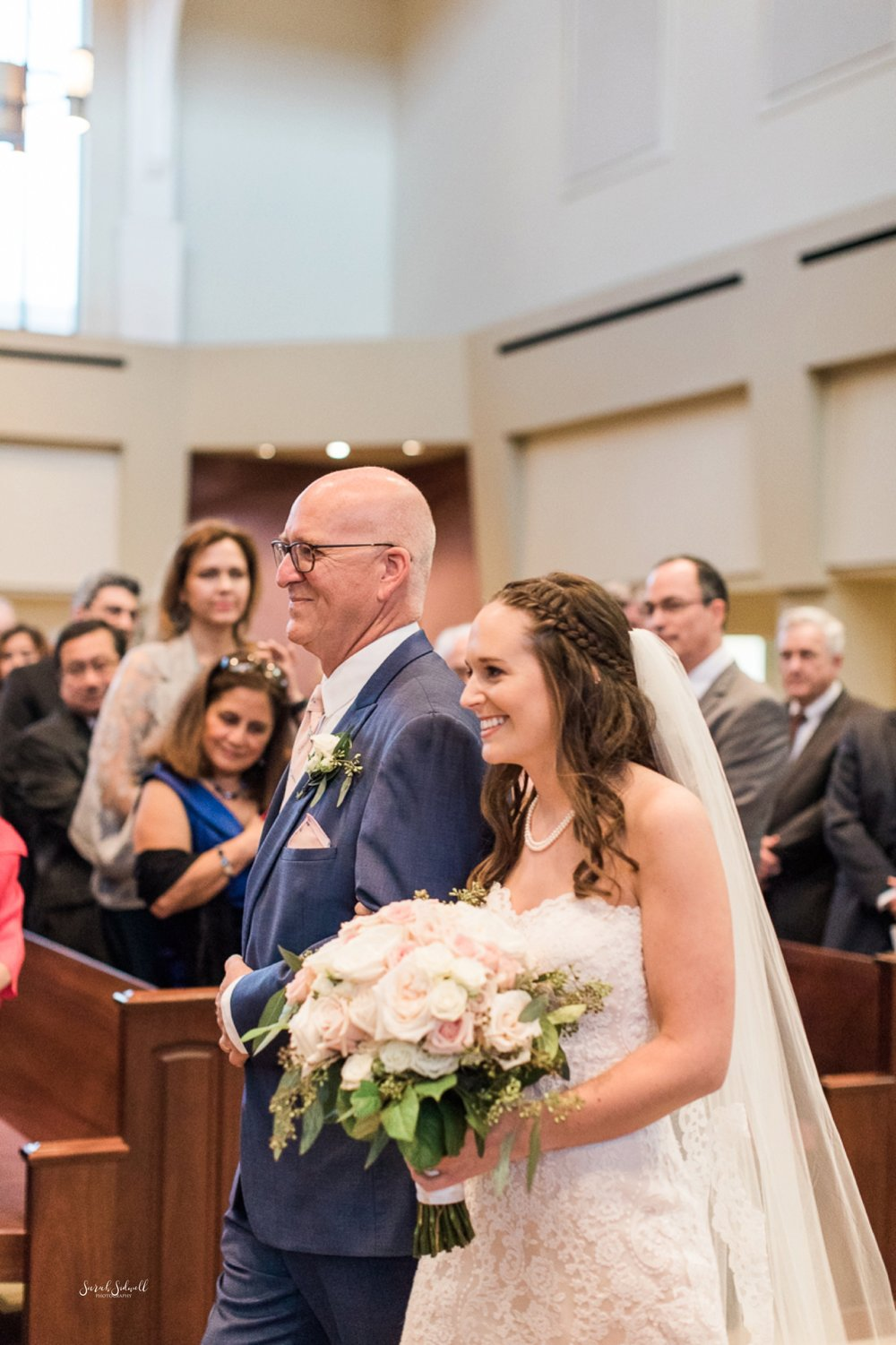 A man walks his daughter down the aisle for her wedding.