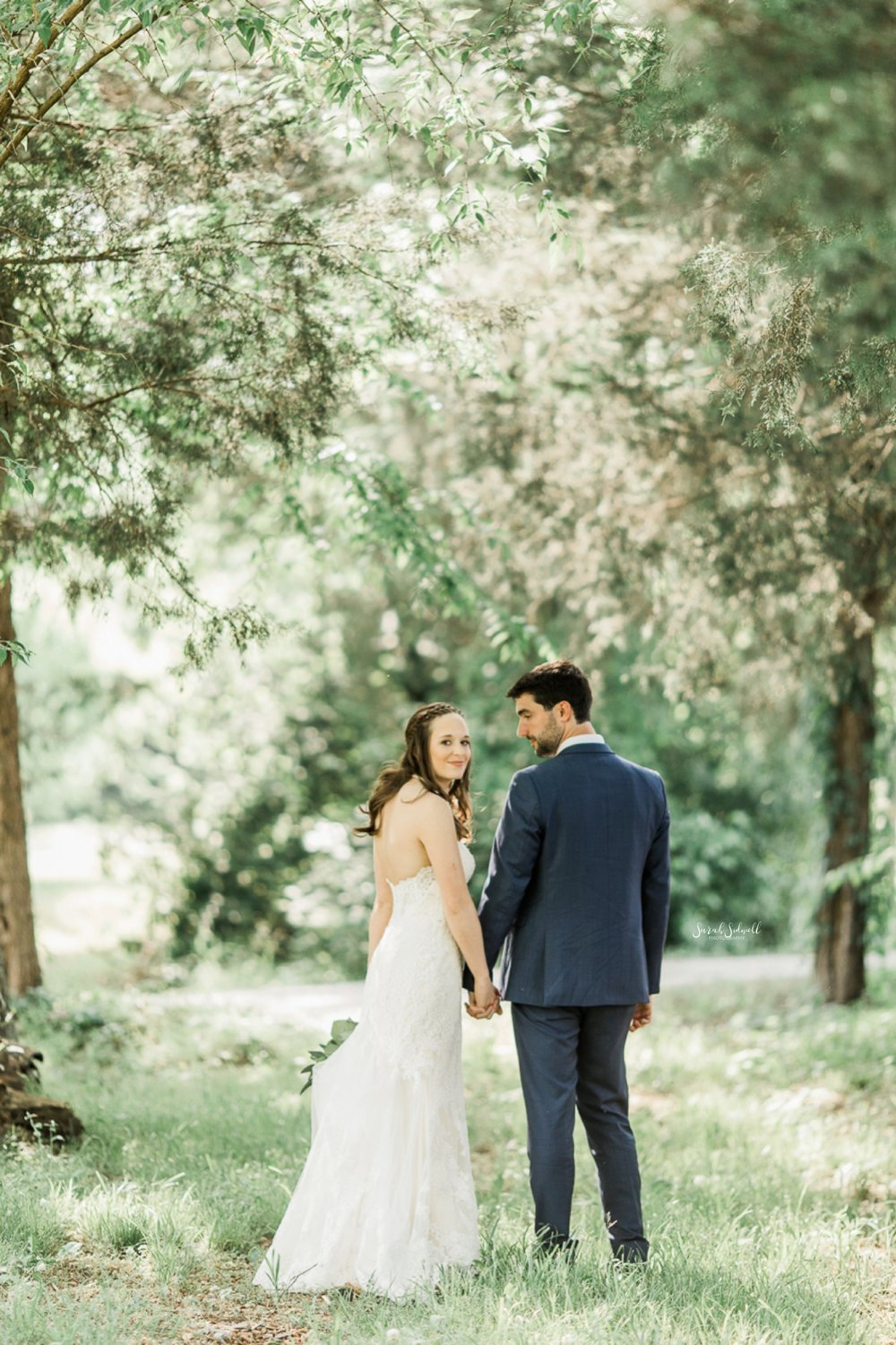 A newlywed couple take a walk under large trees.