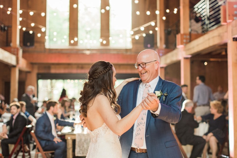 A man dances with his daughter at her wedding.