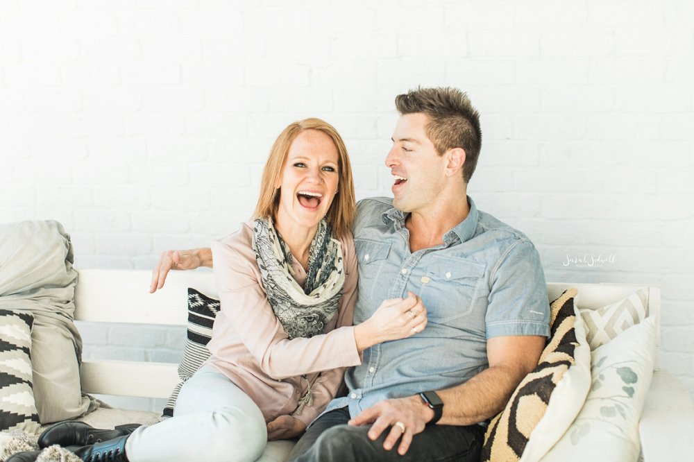 A woman laughs as her husband tells a funny story.