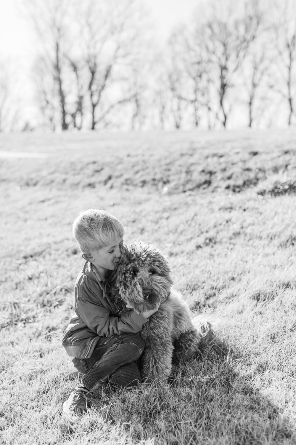 A boy sits in the grass, hugging the neck of his dog.