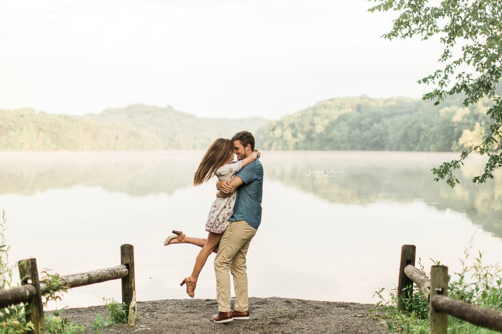 A man lifts his fiance up and hugs her on Radnor Lake.