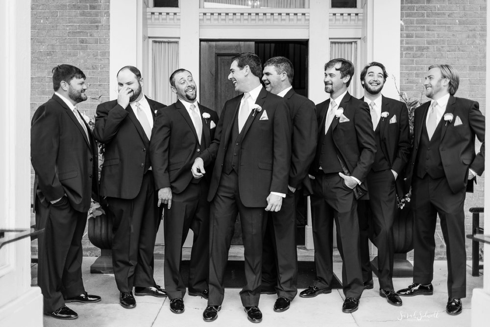 A groom laughs with his groomsmen before the wedding.