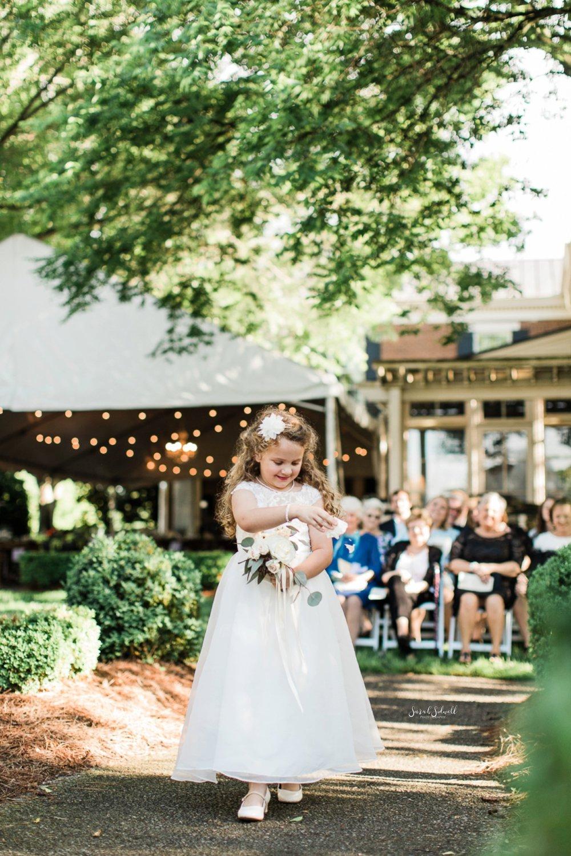 A flower girl walks down the wedding aisle.