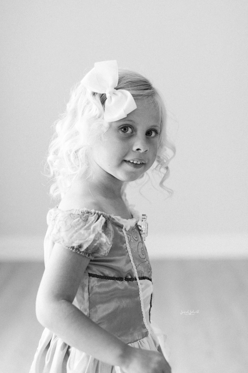 A little girl wears a white bow in her hair.