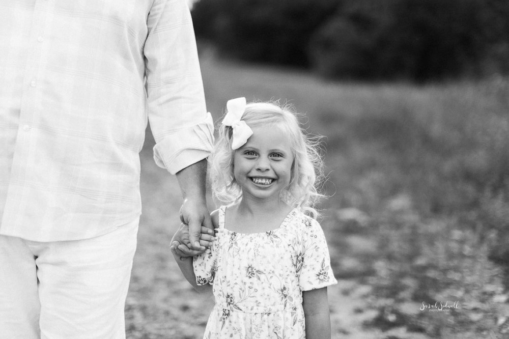 A girl smiles big as she holds her daddy's hand.